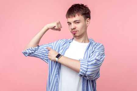 I am strong. Portrait of proud brown-haired man with small beard and mustache in casual shirt pointing at biceps, feeling strength and confidence. indoor studio shot isolated on pink background