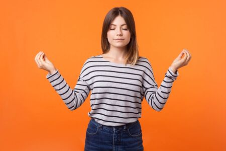 Portrait of calm young woman with brown hair in long sleeve striped shirt standing with closed eyes, meditating with mudra gesture, peaceful mind. indoor studio shot isolated on orange background