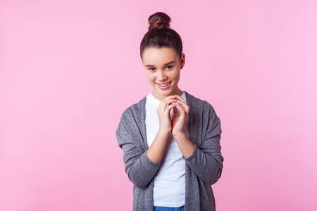 Portrait of funny playful brunette teenage girl with bun hairstyle in casual clothes grinning at camera with cunning sly expression, making tricky plan to prank friend. studio shot pink background