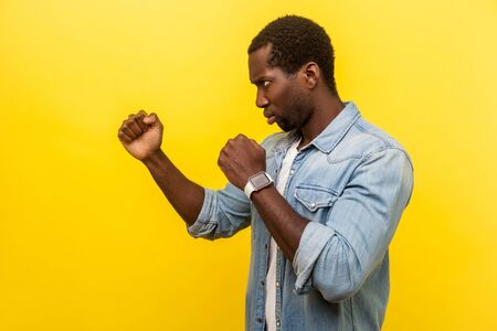 Side view portrait of confident purposeful man in denim casual shirt standing in defensive posture with clenched fists attack, ready to fight, attack. indoor studio shot isolated on yellow background