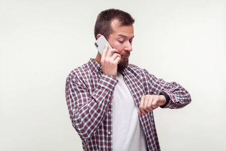 Portrait of punctual bearded man in plaid shirt talking on phone and checking time on wristwatch, dissatisfied with delay, deadline, mobile communication. indoor studio shot isolated, white background