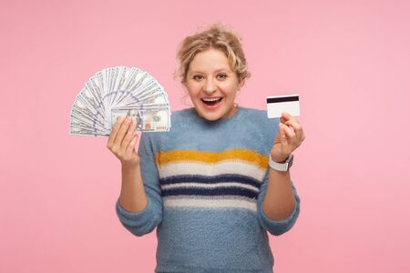 Portrait of surprised and happy adult woman with curly hair in sweater holding dollar banknotes and credit card, looking with shocked astonished expression. studio shot isolated on pink background
