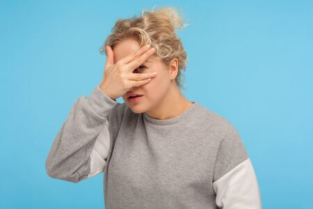 Nosy, inquisitive woman with short curly hair in sweatshirt looking through fingers, peeking interesting rumor or secret, spying with curious expression. indoor studio shot isolated on blue background Stock Photo