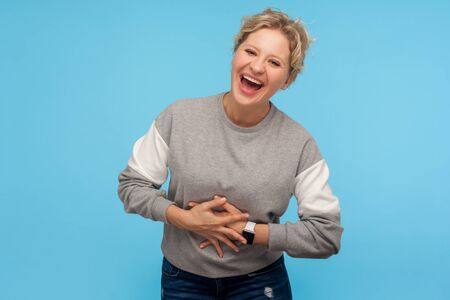 Happiness and laughter. Extremely excited woman with short hair in sweatshirt holding belly and laughing out loudly, cracking up, amused by funny joke. indoor studio shot isolated on blue background