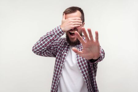 No, don't want to watch! Portrait of scared bearded man in casual plaid shirt closing eyes with hand and gesturing stop i won't look, avoiding problems. indoor studio shot isolated on white background