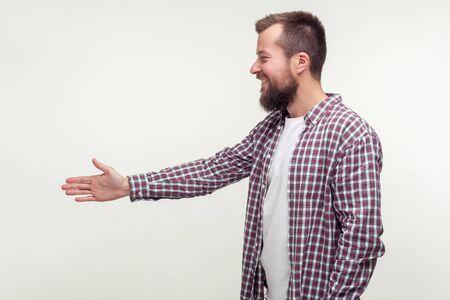 Zijaanzicht van een vriendelijke bebaarde man in een casual geruit hemd die de hand reikt om de hand te schudden, kennis te maken met een sollicitatiegesprek, nieuwe mensen te ontmoeten. indoor studio-opname geïsoleerd op een witte achtergrond