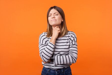 Portrait of ill woman with brown hair in long sleeve striped shirt standing touching neck and frowning from pain, suffering sore throat, flu symptom. indoor studio shot isolated on orange background