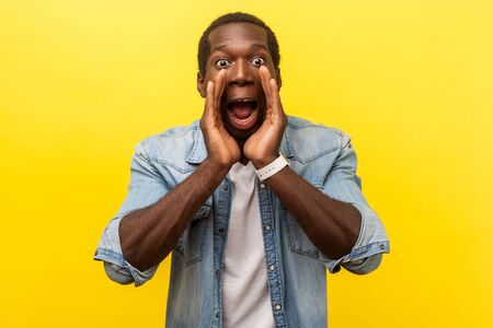 Attention! Portrait of scared man in denim shirt holding hands near wide open mouth and shouting announcement, looking with big eyes, shocked frightened face. studio shot isolated on yellow background