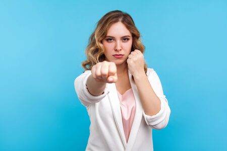 Portrait of determined woman with wavy hair in white jacket punching fist to fight and staring intently at camera, her look expressing confidence and power. studio shot isolated on blue background