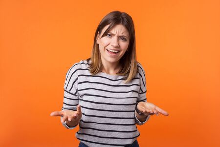 What do you want? Portrait of confused annoyed woman with brown hair in long sleeve shirt raising arms, asking and having no idea what happening. indoor studio shot isolated on orange background Stok Fotoğraf