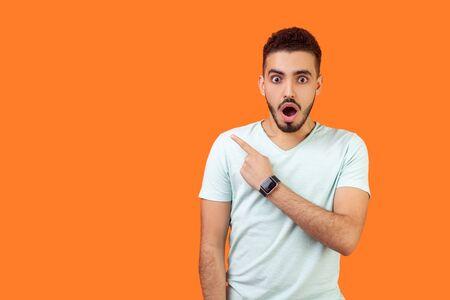 Notizie scioccanti! Ritratto di stupito uomo bruna con la barba in maglietta bianca in piedi con la bocca aperta, guardando sorpreso e indicando a sinistra, spazio vuoto per il testo, pubblicità. ripresa in studio al coperto
