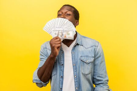 Portrait of greedy young man in denim shirt standing with closed eyes and smelling dollar bills with pleased satisfied expression, hiding half face. indoor studio shot isolated on yellow background