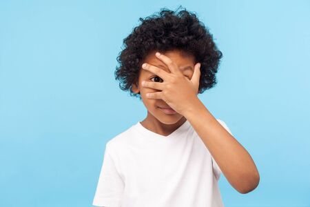 Portrait of funny nosy adorable little boy with curly hair covering face with hand and looking through fingers, curious and shy about watching secret. indoor studio shot isolated on blue background