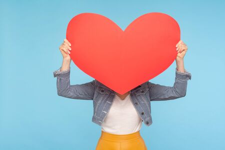 Anonymous woman in casual outfit hiding face behind huge red heart, concept of secret love fondness, unknown lover and affair, romance on Valentines day. indoor studio shot isolated on blue background Stock Photo