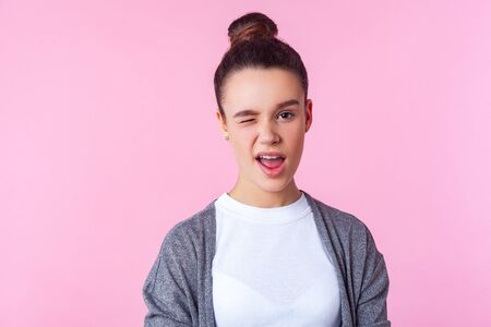 Portrait of playful brunette teenage girl with bun hairstyle in casual clothes winking at camera, looking charming and coquettish, saying hey there. indoor studio shot isolated on pink background