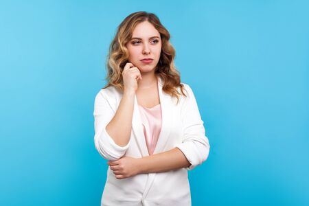 Portrait of thoughtful business woman with wavy hair in white jacket looking away, musing, pondering with confused puzzled face, having doubts. indoor studio shot isolated on blue background