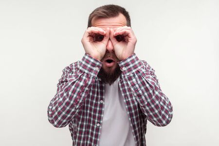 Portrait of curious wondered bearded man in casual plaid shirt looking through fingers gesturing binoculars, amazed surprised by what he discovers. indoor studio shot isolated on white background