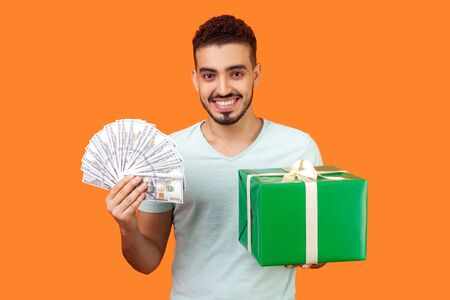 Cashback and credit for shopping. Portrait of cheerful buyer, man with beard in white t-shirt holding gift box and lots of money, smiling at camera. indoor studio shot isolated on orange background