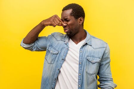 Unpleasant smell. Portrait of young man in denim casual shirt grimacing in disgust and pinching his nose, displeased by bad breath or stinky odor, fart. studio shot isolated on yellow background Stock Photo