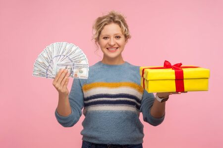 Money and gift. Portrait of beautiful happy woman with curly hair in warm sweater holding present box and dollar bills, satisfied with bonuses, cashback. indoor studio shot isolated on pink background