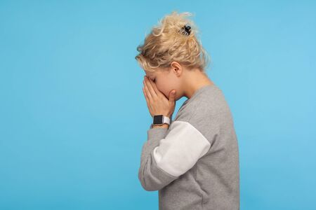 Side view of depressed woman with short curly hair in casual sweatshirt hiding face down in hands and crying, hard going through loss or defeat, feeling sorrow. studio shot isolated on blue background