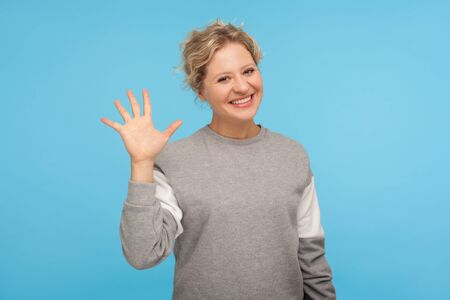 Hello! Cheerful woman with short hair in casual sweatshirt smiling friendly at camera and waving hi, welcoming or showing goodbye, hospitable greeting. indoor studio shot isolated on blue background