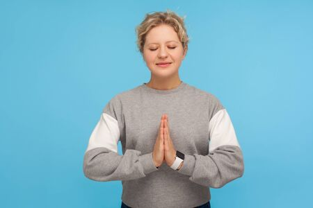Harmony healing, yoga. Tranquil woman with short curly hair in sweatshirt doing namaste gesture and praying with closed eyes, meditation techniques. indoor studio shot isolated on blue background Stock Photo