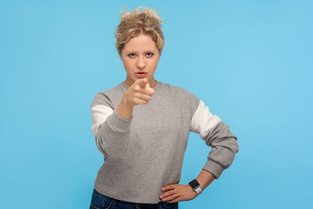 Hey you! Displeased bossy woman with short curly hair in sweatshirt pointing finger to camera and blaming for mistakes, shaming making you guilty. indoor studio shot isolated on blue background