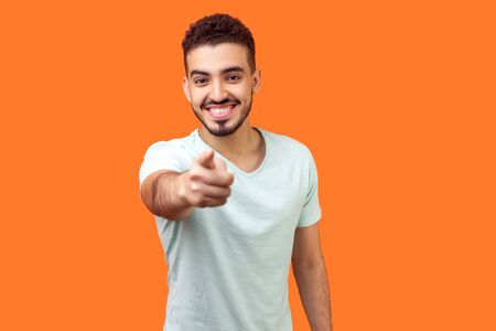 Hey you! Portrait of cheerful handsome brunette man with beard in white t-shirt pointing finger at camera with joyful toothy smile, choosing you. indoor studio shot isolated on orange background