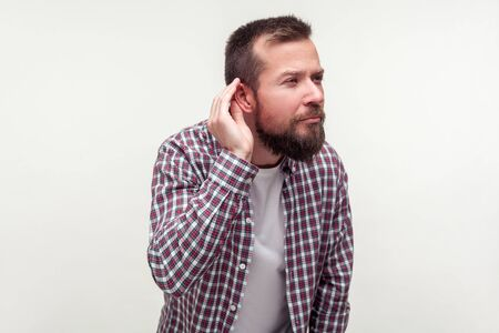 Portrait of deaf bearded man in plaid shirt standing with hand near ear and listening carefully to secret conversation, hearing problems, deafness. indoor studio shot isolated on white background 版權商用圖片