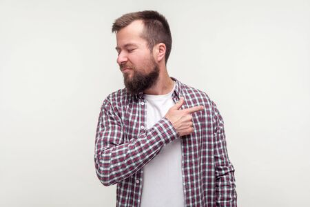 Get out! Portrait of angry bearded man in casual plaid shirt pointing finger to the side and turned away, looking irritated disappointed with your behavior. studio shot isolated on white background Stock Photo