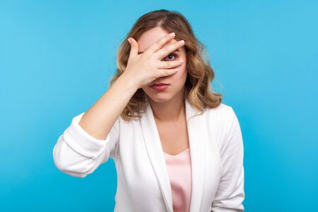 Portrait of young curious woman with wavy hair in white jacket looking through fingers, peeking with serious calm face, having suspicious, watching secrets. studio shot isolated on blue background