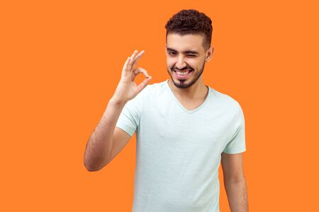 I am ok! Portrait of playful optimistic handsome brunette man with beard in white t-shirt showing okay finger gesture and winking at camera, flirting. indoor studio shot isolated on orange background Stock fotó