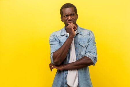 Retrato de hombre pensativo desconcertado en camisa casual de mezclilla con mangas enrolladas mirando hacia arriba y pensando intensamente con expresión incierta de duda. Foto de estudio de interior aislado sobre fondo amarillo Foto de archivo