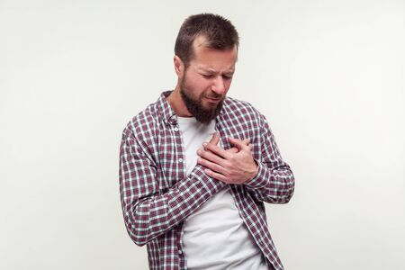 Heart attack, cardiological problems. Portrait of stressed out bearded man in plaid shirt grabbing chest suffering acute pain cramp, risk of infarct. indoor studio shot isolated on white background