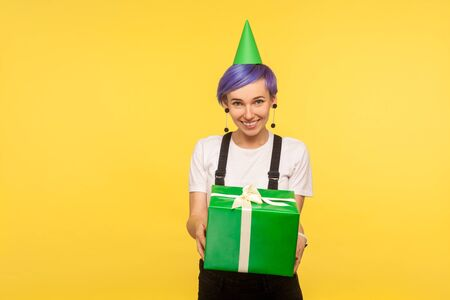 Take birthday present! Portrait of generous cute hipster girl with violet short hair wearing funny party cone and overalls giving present box, congratulating. isolated on yellow background studio shot