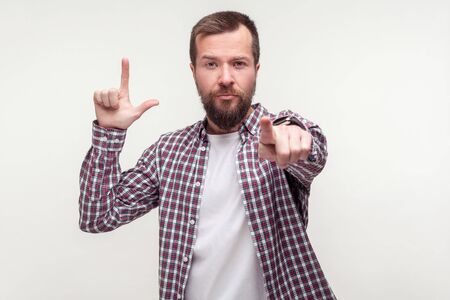 You are loser! Portrait of serious bossy bearded man in casual plaid shirt pointing at camera and showing loser gesture with L finger symbol, accusing. indoor studio shot isolated on white background Banco de Imagens
