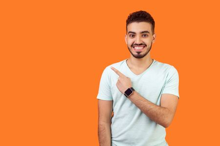 Look here! Portrait of positive friendly brunette man with beard in casual white t-shirt standing pointing at left, empty space for text, advertise. indoor studio shot isolated on orange background