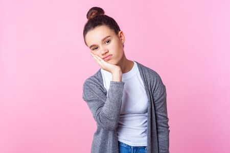 I'm bored. Portrait of depressed brunette teenage girl with bun hairstyle in casual clothes leaning on head, looking tedious tired of everything. indoor studio shot isolated on pink background