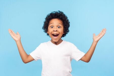 No way, I can't believe! Portrait of funny amazed preschool boy keeping hands up in astonishment, looking surprised and sarcastic at camera, excited shocked by sudden news. studio shot blue background
