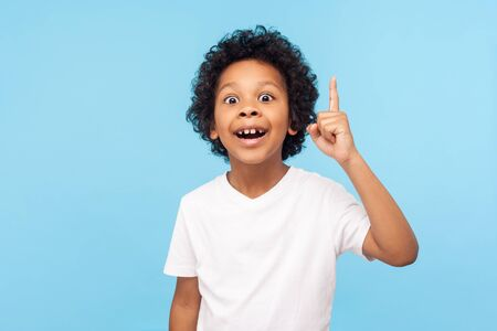Eureka! Portrait of smart little boy with curly hair pointing finger up and looking inspired by genius thought, showing good idea sign, having clever solution in mind. studio shot blue background Stock Photo