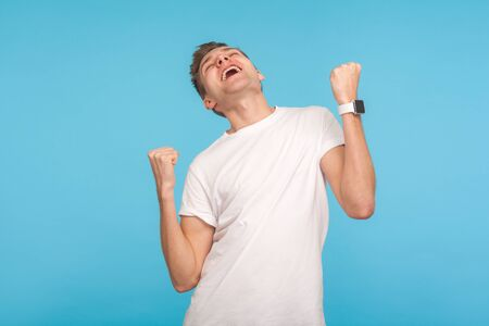 Portrait of victorious ecstatic man in casual white t-shirt screaming yes I'm winner, rejoicing great success, emotionally celebrating victory, triumph. indoor studio shot isolated on blue background