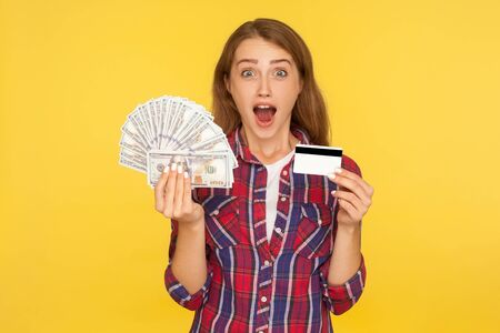 Amazed happy excited ginger girl in shirt standing with plastic bank card and dollar banknotes in her hands, looking surprised shocked at camera. indoor studio shot isolated on yellow background Stock Photo