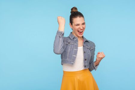 Portrait of excited overjoyed fashionably dressed woman with hair bun standing with raised fists and shouting yeah, I'm winner, rejoicing victory, success. studio shot isolated on blue background