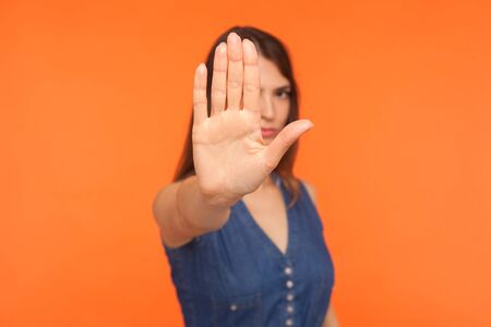 Prohibited! Strict brunette girl with serious bossy expression raising hand and showing stop, caution, warning with raised palm, rejection gesture. indoor studio shot isolated on orange background