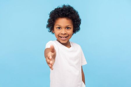 Portrait of friendly cheerful little boy with curly hair in white T-shirt giving hand to handshake and smiling at camera, looking gullible trustful. indoor studio shot isolated on blue background Archivio Fotografico