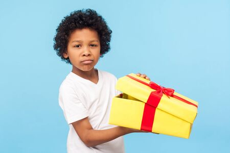 Portrait of funny little boy holding unpacked gift box and looking at camera with upset dissatisfied grimace, naughty capricious child displeased with bad present. indoor studio shot blue background