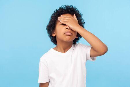 Gesichtspalme. Porträt eines vergesslichen verärgerten kleinen Jungen mit Locken, der das Gesicht mit der Hand bedeckt und sein Bedauern über Fehler ausdrückt, hat vergessen, Hausaufgaben zu machen. Indoor-Studioaufnahme auf blauem Hintergrund isoliert
