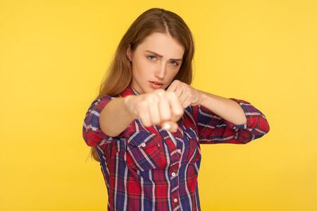 Portrait of strong and determined ginger girl in checkered shirt punching air with fist and looking confidently at camera, female struggle, fighting spirit. studio shot isolated on yellow background