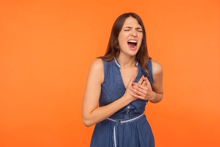 Acute pain in chest. Sick overworked brunette woman clutching and grimacing from painful cramp, heart attack at young age, cardiac disease. indoor studio shot isolated on orange background
